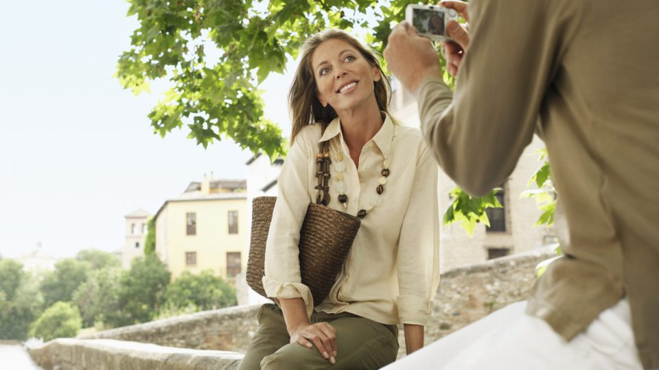 Man taking picture of happy woman on wall in Granada; Spain
