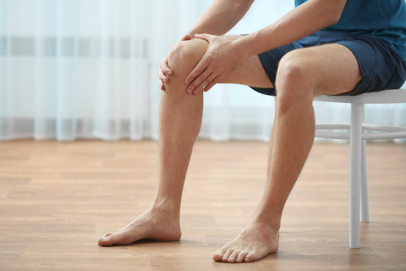 Young man suffering from knee pain at home